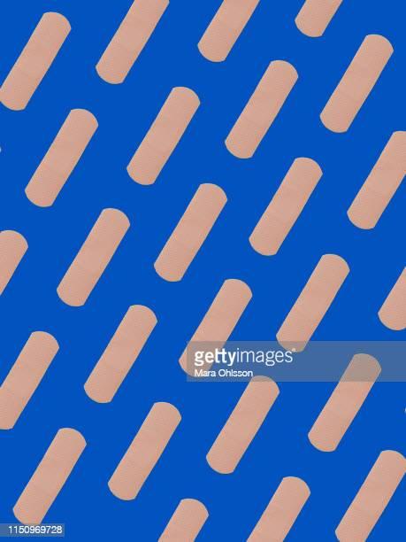 first aid adhesive plasters in diagonal pattern on blue background - esparadrapo fotografías e imágenes de stock