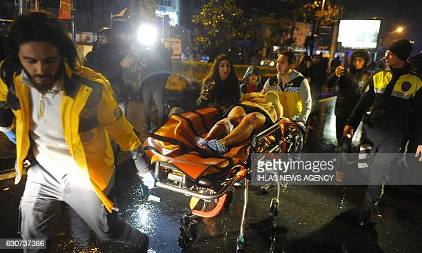TOPSHOT First aid officers carry an injured woman at the site of an armed attack on January 1 2017 in Istanbul At least two people were killed in an...
