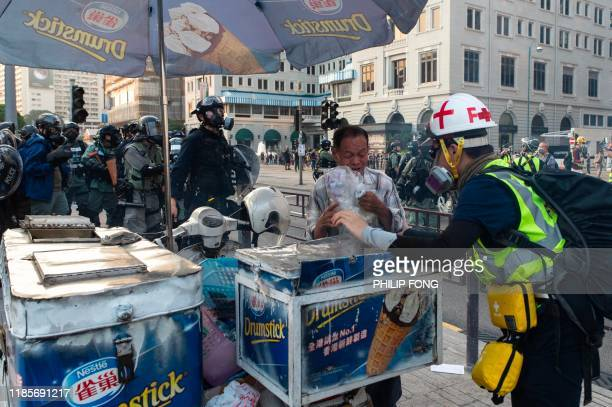 First aid volunteer helps an ice-cream vendor pack up his stall after police fired tear gas during a march from the Tsim Sha Tsui district to Hung...