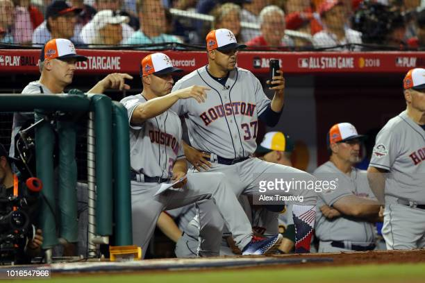 First base coach Alex Cintron of the Houston Astros uses his phone in the dugout during the 89th MLB AllStar Game at Nationals Park on Tuesday July...