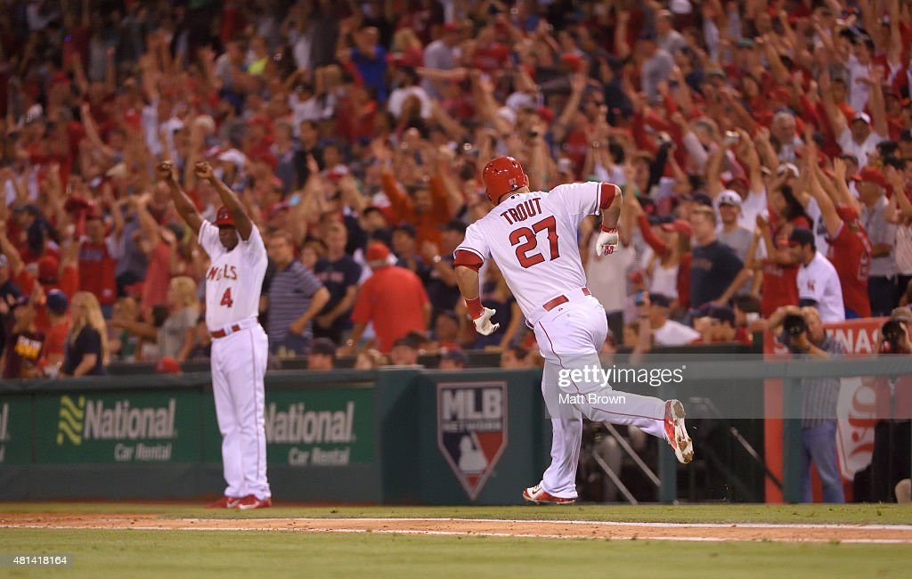 First base coach Alfredo Griffin #4 and Mike Trout #27 of the Los Angeles Angels of Anaheim celebrate after Trout hit a walk-off home run in the bottom of the ninth inning to defeat the Boston Red Sox 1-0 at Angel Stadium of Anaheim on July 17, 2015 in Anaheim, California.
