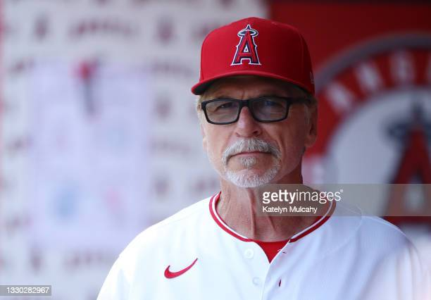 First base coach Bruce Hines of the Los Angeles Angels looks on from the dugout before the game against the Seattle Mariners at Angel Stadium of...
