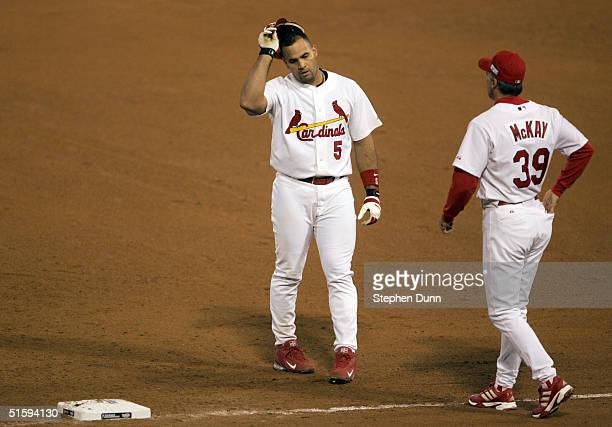 First base coach Dave McKay looks on as Albert Pujols of the St Louis Cardinals reacts after popping out to end the sixth inning during game four of...