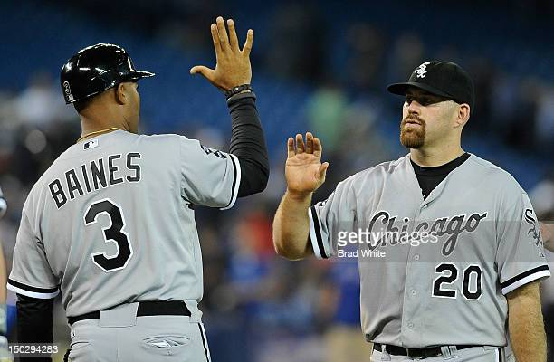 First Base Coach Harold Baines of the Chicago White Sox celebrates the teams win with teammate Kevin Youkilis during MLB game action against the...