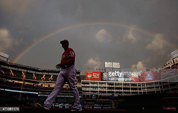 First base coach Hector Ortiz of the Texas Rangers walks to the dugout as the Rangers prepare to take on the Seattle Mariners after a rain delay at...