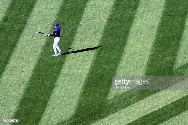 First base coach John Shelby of the Los Angeles Dodgers hits a ball back to the infield during batting practice before the game against the Chicago...