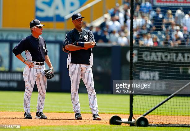 First base coach Mick Kelleher and Derek Jeter of the New York Yankees stand in the infield during batting practice before the start of their game...