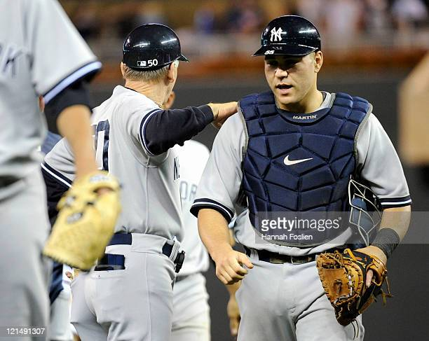 First base coach Mick Kelleher and Russell Martin of the New York Yankees celebrate a win against the Minnesota Twins on August 19 2011 at Target...