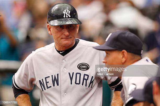 First base coach Mick Kelleher of the New York Yankees talks with Alex Rodriguez in the dugout during the game between the New York Yankees and the...