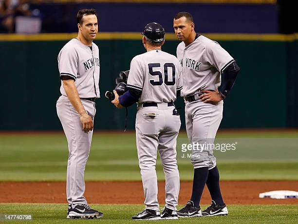 First base coach Mick Kelleher of the New York Yankees talks with Mark Teixeira and Alex Rodriguez after an inning ending double play against the...