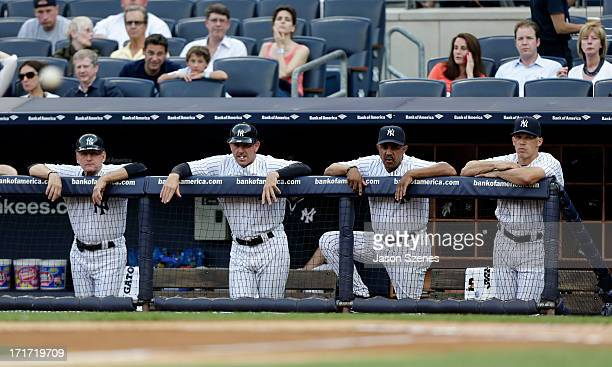 First base coach Mick Kelleher third base coach Rob Thomson bench coach Tony Pena and manager Joe Girardi of the New York Yankees are seen against...
