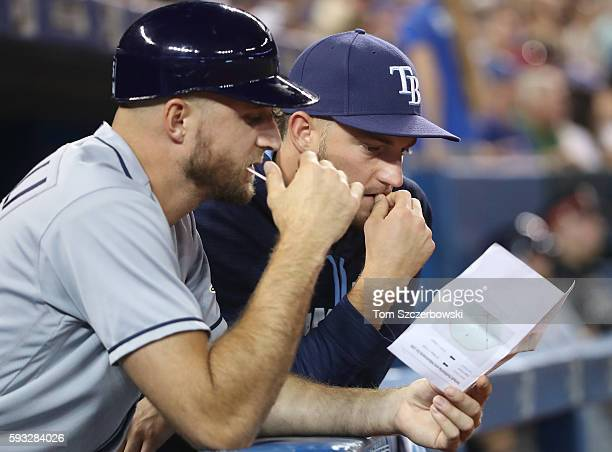 First base coach Rocco Baldelli of the Tampa Bay Rays and Matt Andriese examine hitter spray charts on the top step of the dugout during MLB game...