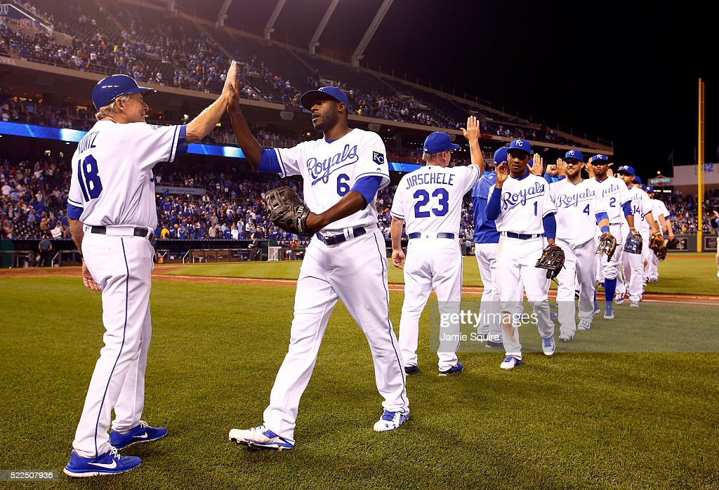 First base coach Rusty Kuntz #18 and Lorenzo Cain #6 of the Kansas City Royals high five as the rest of the team celebrates on the field after the Royals defeated the Detroit Tigers 8-6 to win the game at Kauffman Stadium on April 19, 2016 in Kansas City, Missouri.