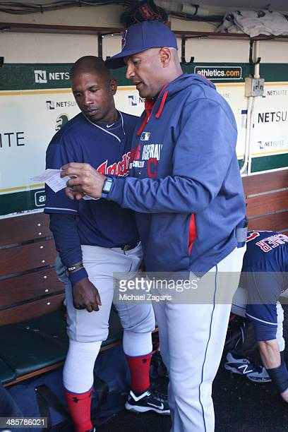 First Base Coach Sandy Alomar Jr #15 of the Cleveland Indians talks with Nyjer Morgan in the dugout prior to the game against the Oakland Athletics...