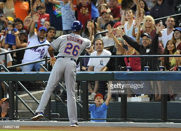 First Base Coach Tom Goodwin of the New York Mets throws a ball to some fans late in a game against the Arizona Diamondbacks at Chase Field on July...