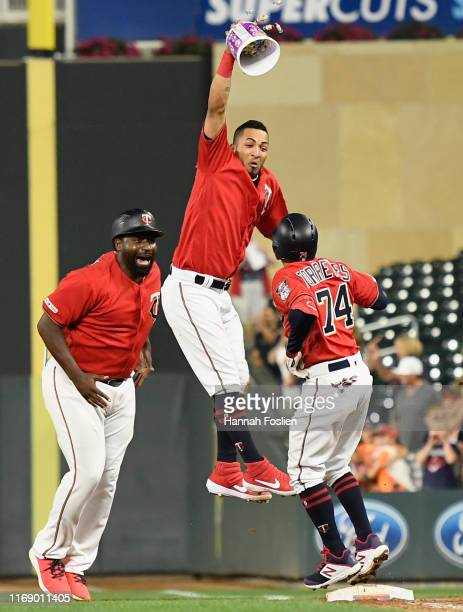 First base coach Tommy Watkins and Eddie Rosario of the Minnesota Twins congratulate teammate Ronald Torreyes on a walkoff hit by pitch against the...