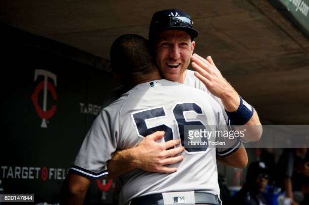 First base coach Tony Pena of the New York Yankees greets Todd Frazier in the dugout during the game against the Minnesota Twins on July 19 2017 at...