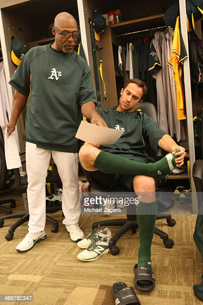 First Base Coach Tye Waller of the Oakland Athletics goes over defense with Sam Fuld in the clubhouse prior to the game against the Cleveland Indians...