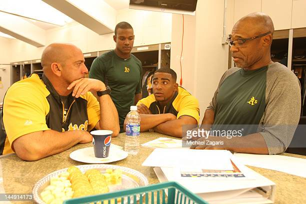 First Base Coach Tye Waller of the Oakland Athletics talks with translator Ariel Prieto Yoenis Cespedes and Michael Taylor in the clubhouse prior to...