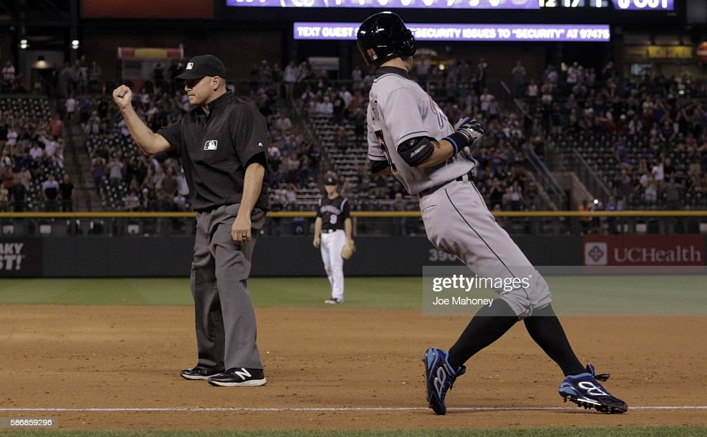 First base umpire Andy Fletcher, left, calls out Ichiro Suzuki #51 of the Miami Marlins in the ninth inning against the Colorado Rockies at Coors Field on August 6, 2016 in Denver, Colorado. Ichiro got the 2,999th hit his Major League Baseball career in the previous at-bat.