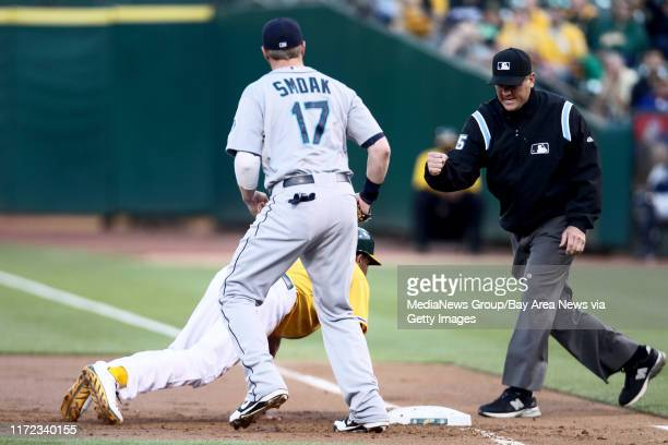 First base umpire Chad Fairchild calls out to Oakland Athletics' Chris Young after he was picked up by Seattle Mariners' Justin Smoak in the first...