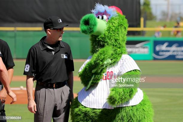 First base umpire Dan Iassogna talks with the Phillie Phanatic moments before the start of the spring training game between the Pittsburgh Pirates...