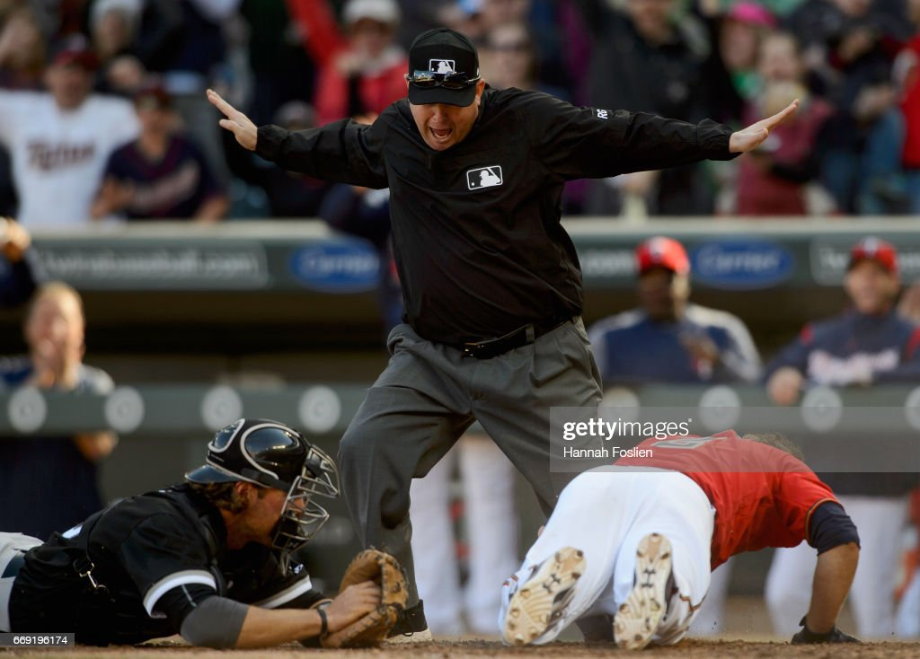 First base umpire Todd Tichenor #13 covering the plate calls Brian Dozier #2 of the Minnesota Twins safe on an inside-the-park home run as Kevan Smith #36 of the Chicago White Sox looks on during the fifth inning of the game on April 16, 2017 at Target Field in Minneapolis, Minnesota.