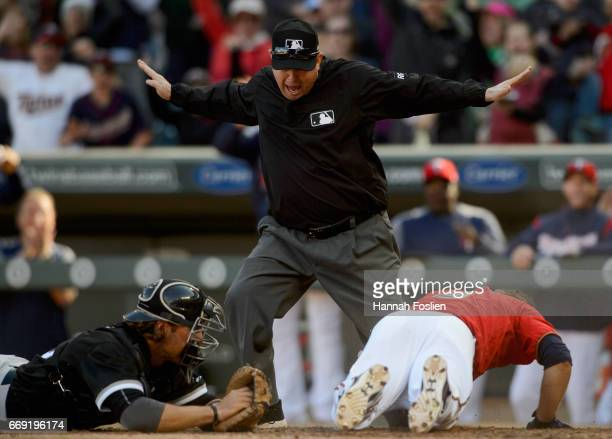 First base umpire Todd Tichenor covering the plate calls Brian Dozier of the Minnesota Twins safe on an insidethepark home run as Kevan Smith of the...