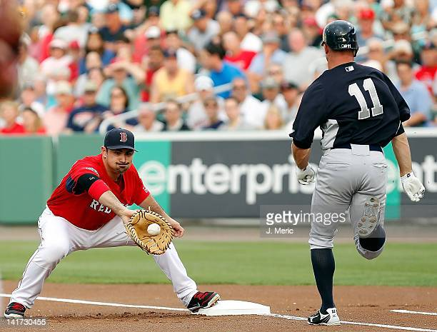 First baseman Adrian Gonzalez of the Boston Red Sox takes the throw at first as outfielder Brett Gardner of the New York Yankees is out during a...