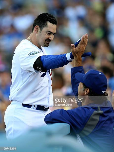 First baseman Adrian Gonzalez of the Los Angeles Dodgers high fives with manager Don Mattingly as he returns to the dugout after hitting a three run...