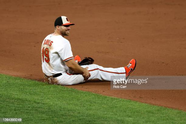 First baseman Chris Davis of the Baltimore Orioles sits on the ground after fielding a ball against the Miami Marlins at Oriole Park at Camden Yards...