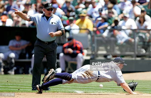 First baseman Chris Shelton of the Detroit Tigers can't reach a ball hit by the Oakland Athletics as first base umpire Bob Davidson signals fair ball...