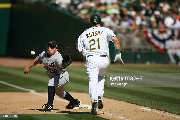 First baseman Chris Shelton of the Detroit Tigers catches a throw at first base during the game against the Oakland Athletics as A's base runner Mark...