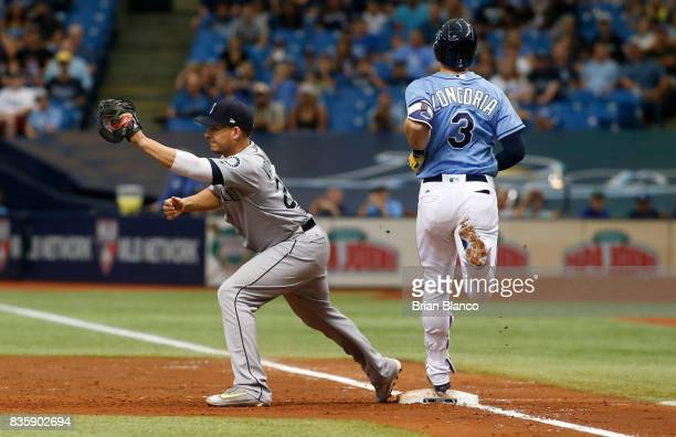 First baseman Danny Valencia of the Seattle Mariners hauls in the throw from second baseman Robinson Cano to complete the double play with the out on...