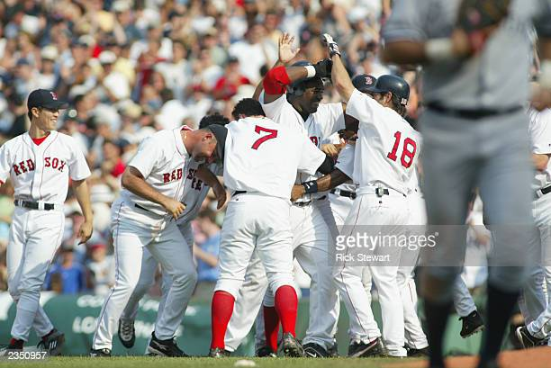 First baseman David Ortiz of the Boston Red Sox celebrates with teammates right fielder Trot Nixon and center fielder Johnny Damon after driving in...
