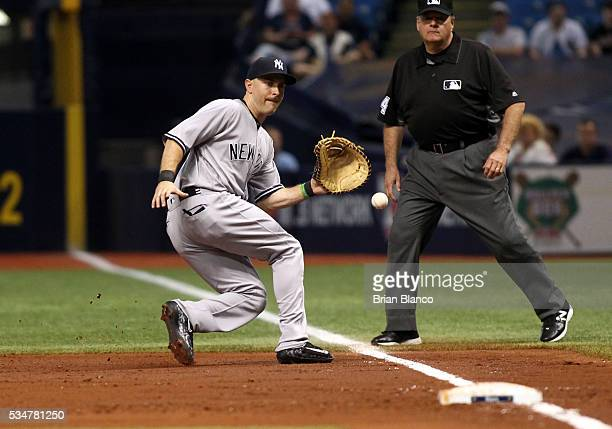 First baseman Dustin Ackley of the New York Yankees fields the ground out by Hank Conger of the Tampa Bay Rays to end the third inning of a game on...