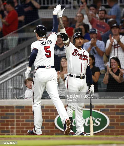 First baseman Freddie Freeman of the Atlanta Braves is congratulated by third baseman Johan Camargo after Freeman hit a home run in the third inning...