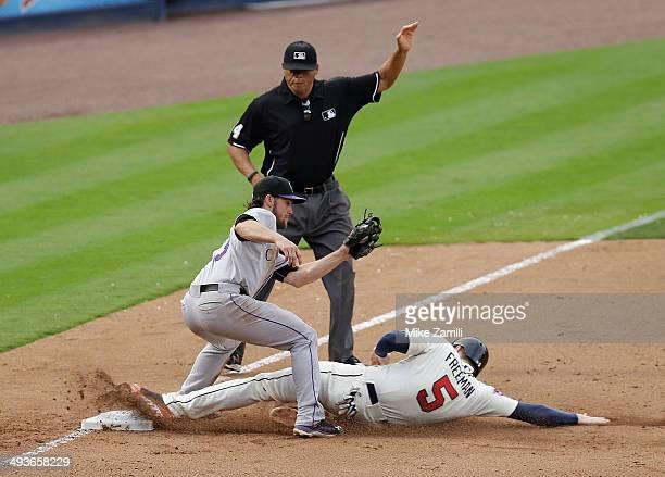 First baseman Freddie Freeman of the Atlanta Braves slides into third base under the tag of third baseman Charlie Culberson of the Colorado Rockies...