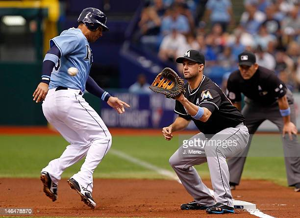 First baseman Gaby Sanchez of the Miami Marlins takes the throw at first as Carlos Pena of the Tampa Bay Rays gets back safely during the interleague...