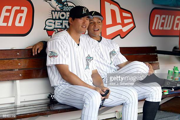 First baseman Hee Seop Choi and right fielder Miguel Cabrera of the Florida Marlins sit in the dug out and watch the Marlins Mermaids before the...