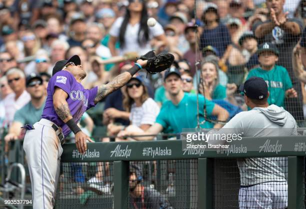 First baseman Ian Desmond of the Colorado Rockies reaches over the dugout railing to catch a pop fly by Mitch Haniger of the Seattle Mariners during...