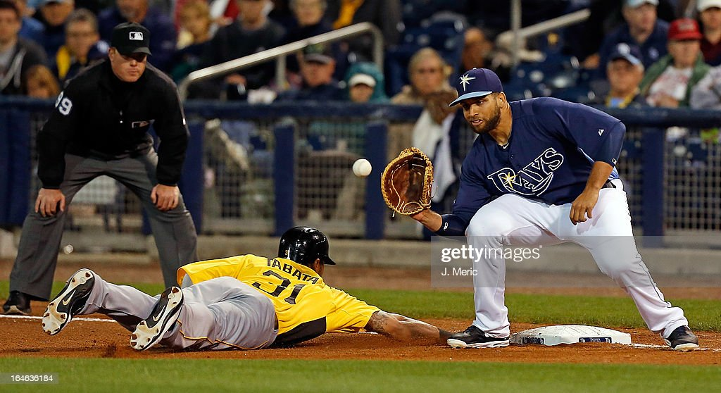 First baseman James Loney #21 of the Tampa Bay Rays takes the throw at first as outfielder Jose Tabata #31 of the Pittsburgh Pirates gets back safely during a Grapefruit League Spring Training Game at the Charlotte Sports Complex on March 25, 2013 in Port Charlotte, Florida.