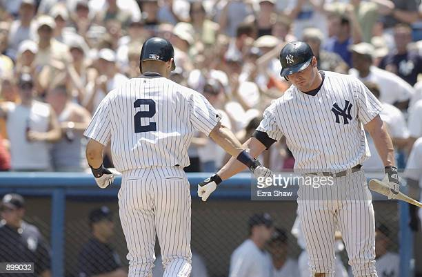 First Baseman Jason Giambi of the New York Yankees congratulates shortstop Derek Jeter as he returns to the dugout after hitting his 11th home run of...