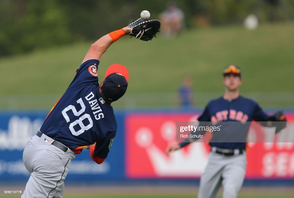 First baseman J.D. Davis #28 of the Houston Astros makes a catch on a ball hit by Todd Frazier #21 of the New York Mets during the first inning of a spring training game at First Data Field on March 6, 2018 in Port St. Lucie, Florida. The Mets defeated the Astros 9-5.