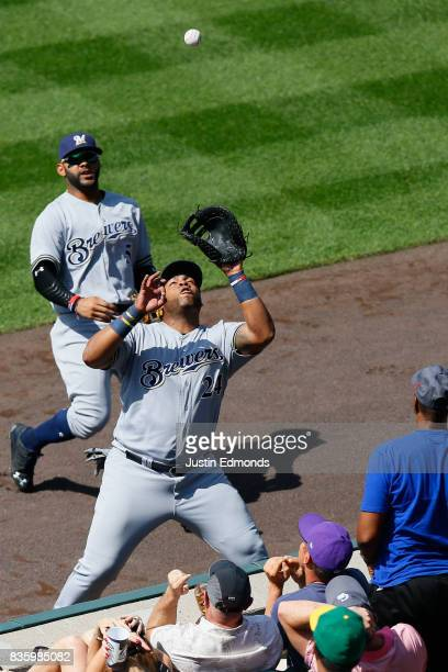 First baseman Jesus Aguilar of the Milwaukee Brewers makes a catch in foul territory as second baseman Jonathan Villar looks on for the third out of...
