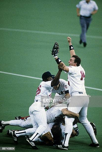 First baseman Kent Hrbek of the Minnesota Twins gets tackled by Al Newman and other teammates with jubilation after he recorded the last out at first...
