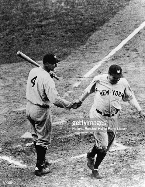 First baseman Lou Gehrig of the New York Yankees shakes hands with teammate Babe Ruth as he crosses the plate during a 1932 World Series game against...