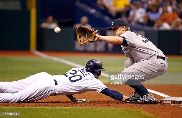 First baseman Mark Reynolds of the New York Yankees takes the throw as Matt Joyce of the Tampa Bay Rays gets back safely during the game at Tropicana...