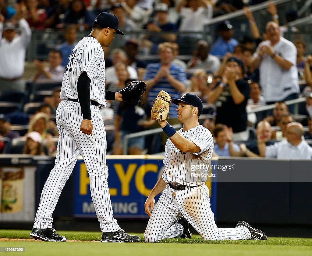 First baseman Mark Teixeira #25 of the New York Yankees is congratulated by pitcher Dellin Betances #68 after Teixeira made a diving reach to first base to get Josh Reddick #22 of the Oakland Athletics during the eighth inning of a MLB baseball game at Yankee Stadium on July 8, 2015 in the Bronx borough of New York City. The Yankees defeated the A's 5-4.