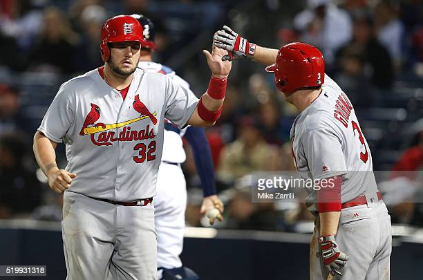 First baseman Matt Adams of the St. Louis Cardinals is congratulated by shortstop Jedd Gyorko after Adams scored on a wild pitch in the fourth inning...
